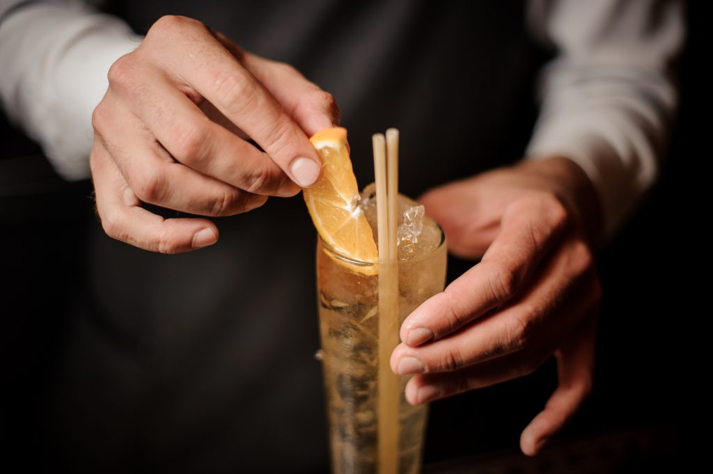 Barman decorating sweet and fresh summer cocktail with a slice of fresh orange and wooden straw