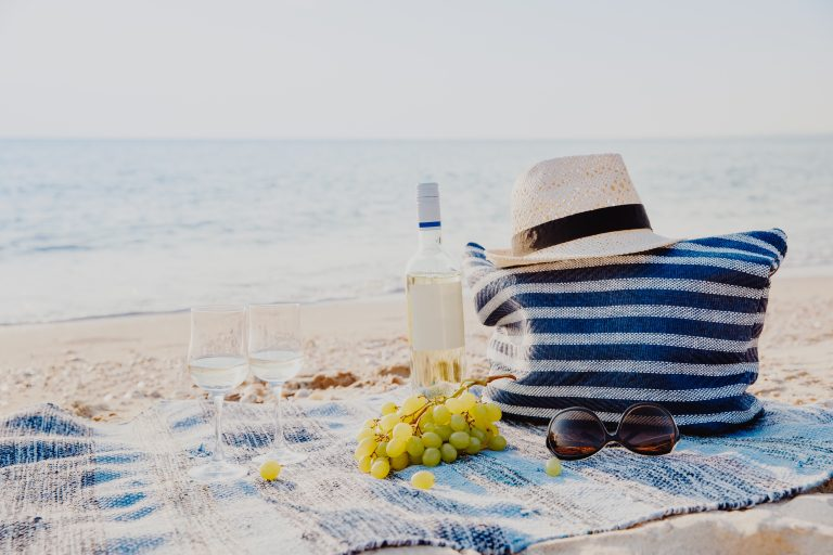 Picnic background with bag, grape and white wine on the beach by blue sea